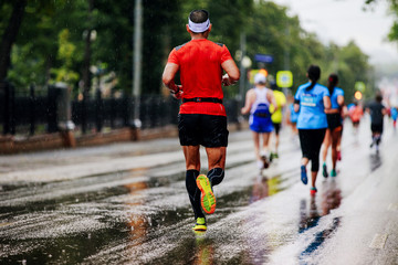 Fototapete - back group runners athletes running marathon in rain