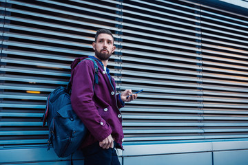 Confident bearded man holding in and mobile phone while standing near street wall in sunny summer evening.