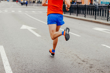Fototapete - back man runner in bright sportswear running city