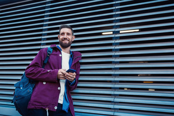 Outdoor fall or winter portrait of handsome hipster man with beard, white t-shirt, blue shirt and maroon jacket holding smartphone