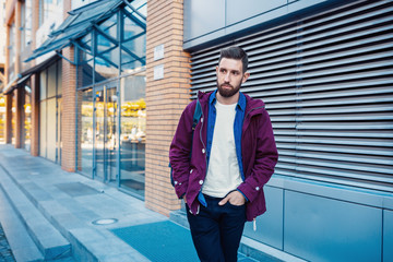 Half length portrait of handsome bearded man dressed in fashionable clothes standing on street.
