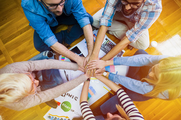 Top view of people crossing hands while sitting on the floor. Team work.