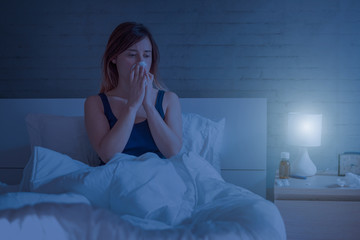Woman blowing nose lying in the bed