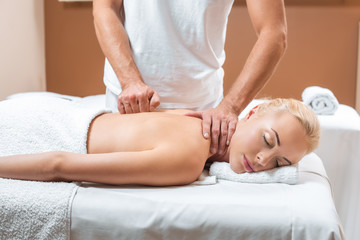 male masseur doing massage to beautiful woman with closed eyes in spa