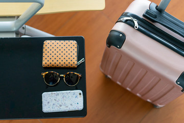 Pink suitcase near table with sunglasses and smartphone