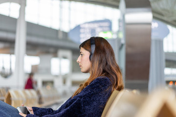 Young woman with headphones using smartphone on chair in lounge