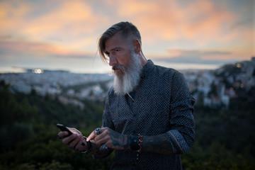 Porträteines attraktiven bärtigen Mannes in Athen auf dem Berg, gegenüber der Akropolis, mit einer Smartphone in der Hand