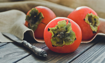 Bright juicy persimmon on the background of a wooden table. Winter fruits