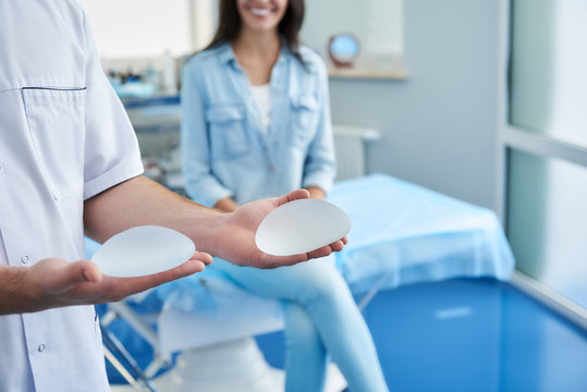 Smiling happy woman sitting on medical couch while doctor showing options for implants