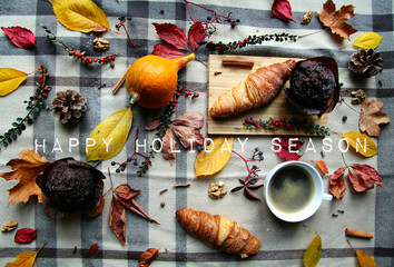 Autumn Background With Chocolate Muffin, Croissant, Leaves With Happy Holiday Season Sign Rustic