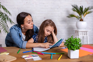 Mother becoming frustrated with daughter whilst doing homework sitting at the table at home in learning difficulties homework.