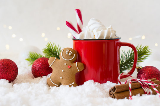 Cozy winter composition with a cup of hot chocolate with marshmallows gingerbread man cookies  on a light festive background.