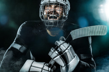 Happy ice hockey player man in the mask and gloves on stadium with stick celebrates victory. Male closeup portrait.