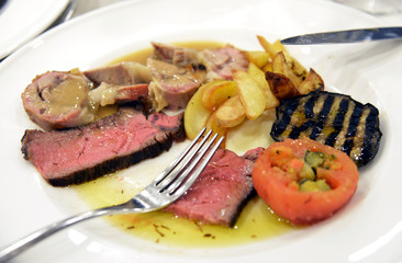 Plate of sliced meat with aubergines tomatoes and potatoes