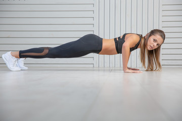 Beautiful young woman doing exercises on the floor to strengthen her muscles, studio portrait