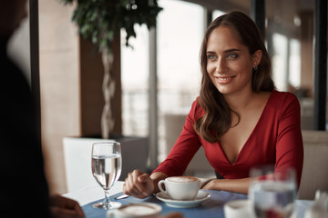 Concept of lovely date. Waist up portrait of smiling ledy in red dress looking at young gentleman while sitting in restaurant with cup of coffee