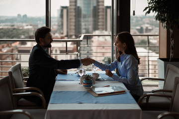 Have successful business deal. Waist up portrait of young male and female work partners shaking hands after concluding agreement during lunch in restaurant