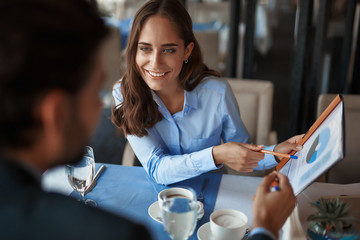 Business lunch in friendly atmosphere. Close up portrait of young smiling businesswoman explaining work project to her male colleague in restaurant