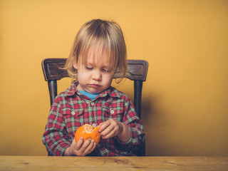 Toddler peeling clementine
