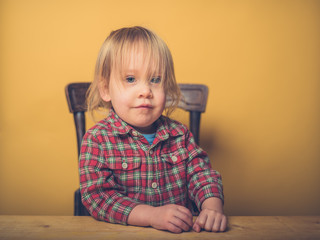 Little toddler sitting at a table