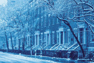 Snowy street scene of historic buildings along Washington Square Park in New York City during winter blizzard in blue