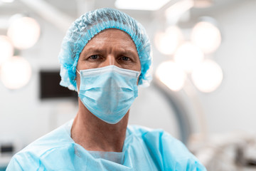 Close up of serious middle aged doctor in blue medical uniform looking at you and frowning