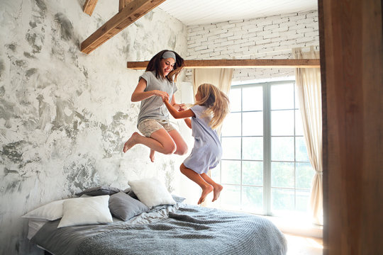 Happy young woman and her little cute daughter are having fun in bed while being at home together