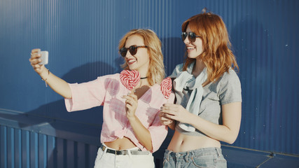 Two young attractive women in sun glasses talking, eat lollipop and take a selfie on street