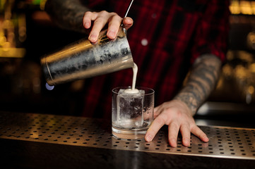 Barman pouring fresh creamy alcoholic drink into a glass