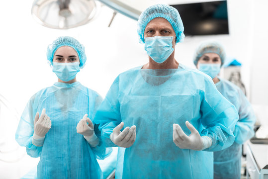 You are in good hands. Waist up portrait of medical workers in protective masks and sterile gloves looking at camera while posing in hospital