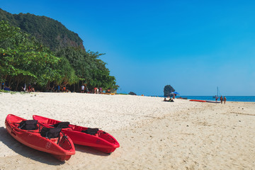 Red Kayaks on the Phra Nang Cave Beach, Railay in Krabi province, Thailand. Kayaking is a popular tourist activity and kayaks can be rented at Railay Beach
