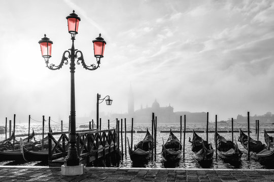 Black and white photo of gondolas in Venice at sunrise with Saint Giorgio island in morning fog, as seen from San Marco square