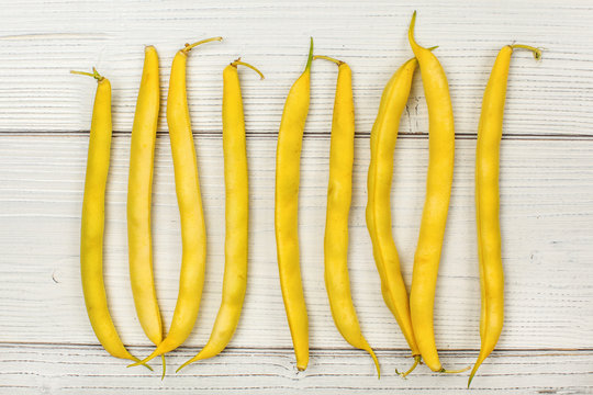 Tabletop view - yellow string (wax) beans on white boards.