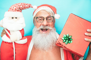 Happy trendy santa claus holding gift and christmas puppet - Fashion sanior man having fun wearing xmas costume - Concept of holiday, culture and winter vacation