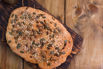 Bread with seeds. Homemade pastries are healthy and tasty. Healthy food and photo in rustic style. Wooden background and food. View from above.