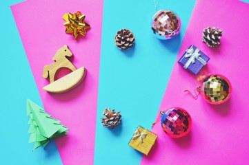 Flat lay Christmas decoration. Balls, wooden horse, pine cones, origami tree. New Year holidays