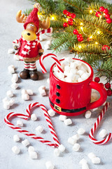 Mug filled with hot chocolate and marshmallows and candy cane
