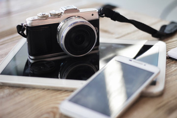 Compact digital photo camera on a wooden table with cup of coffee. Simple composition, soft focus