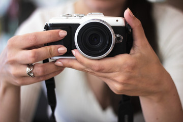 Young woman holds a compact photo camera
