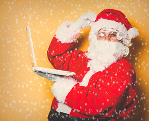 Funny Santa Claus have a fun with laptop on yellow background