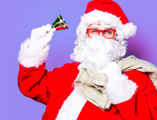 Funny Santa Claus have a fun with bell on purple background