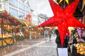 Holiday cityscape - view of star in the form of decoration on background of the Christmas Market (Weihnachtsmarkt) in the city of Bonn, Germany