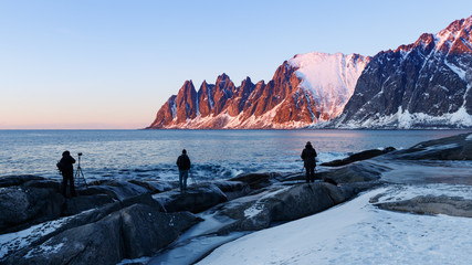 Senja island, Norway. Three photographers with tripods taking pictures of sunset and  waiting for Northern Lights.