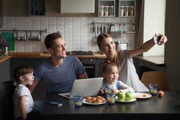Happy large family at breakfast taking selfie, photographing on phone, having breakfast together on kitchen, smiling children, mom and dad posing for family photo at home