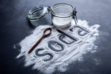 baking soda scattered from a glass jar on a dark background