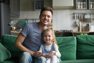 Portrait of happy smiling father with preschool daughter, father sitting on sofa at home together with little girl, kid sitting near dad, look at camera