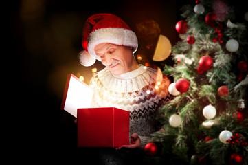 Senior man with a present box next to the christmas tree