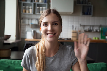 Portrait happy smiling young woman waving hand in the kitchen, looking at camera, greeting, saying hello, head shot portrait