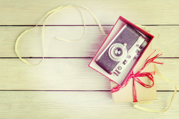 Vintage camera in red gift box, top view. Instagram filtered.