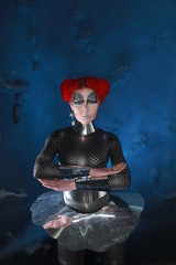 Pretty RedHaired Futuristic Girl With FaceArt Make-Up Wearing Spandex Catsuit and Steel Corset